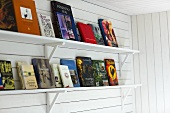 Books on shelves with brackets on white wood paneling