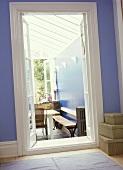 Blauer Flur mit offener Tür und Blick in Wintergarten auf Tisch und Bank