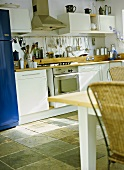 A detail of a modern kitchen diner with white units, stainless steel integral oven, table, cane chairs