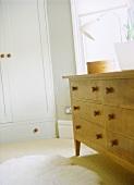 Schlafzimmer mit einer Holzkommode und weißem Kleiderschrank