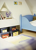 A detail of a child's bedroom with a painted bed, toy storage boxes