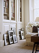 A detail of a traditional, neutral sitting room, built in bookcases, collection of framed photographs leaning against cupboard, natural flooring