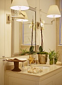 A detail of a traditional bathroom, showing a wash basin set in a unit, mirror, wall lights, gold mirror