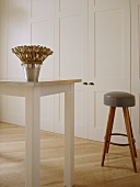 A detail of a modern, country kitchen with dining area, painted units, table, wood stool with leather seat, wood floor, dried seed arrangement