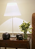 A detail of a modern sitting room showing a polished wood side table, lit steel lamp with white shade, ornaments, flower arrangement
