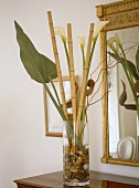 Plant leaves and bamboo with lilies in glass vase