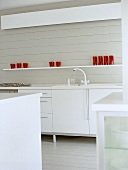Modern white kitchen with red glassware on shelf above cupboard units.
