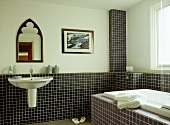 Wall mounted washbasin and bath in tiled bathroom