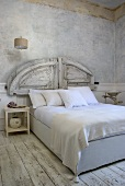 A modern double bed with a rustic headboard and white bedclothes