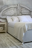 A bed with a rustic, white-painted headboard and white bed clothes