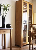 A modern dining room, wooden side table, freestanding display cabinet, flower arrangement,