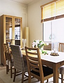 A modern dining room in neutral colours, wooden dining table, chairs, window, venetian blinds, display cabinet, vase, flowers,