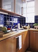 A detail of a modern kitchen, wood units, sink, blue tiling, glass fronted cupboards,