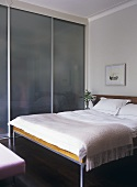 A modern, minimalist bedroom decorated in neutral colour, double bed, fitted wardrobe with sliding door,