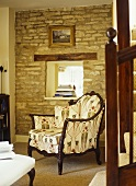 Hallway armchair with patterned fabric under a small window.