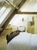 Beamed attic bedroom with a double bed and armchair.