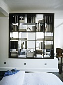 A bookshelf partition dividing a bedroom