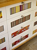 Storage drawers with steel handles and fabric set in drawer fronts