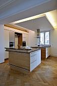Designer Küche mit Kochinsel unter indirekter Beleuchtung und Fischgrätparkett
