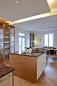 Double central island units in contemporary kitchen in front of display cabinet