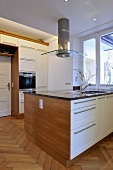 Extractor fan above central island unit in contemporary kitchen
