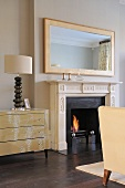 Lamp on chest of drawers next to traditional style fireplace with lit fire in contemporary sitting room