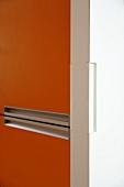 Küchenschrank mit orangefarbener Front und eingelassener Griffmulde