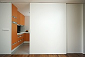 A modern kitchen with orange units and half open white sliding doors