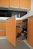Offener Küchenunterschrank mit orangefarbener Front und Edelstahltöpfen
