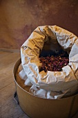 Open paper bag with dried petals in a wooden container