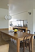 Pendant light above wooden table in modern open plan dining room