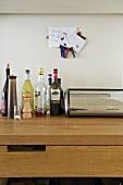 Bottles and bread bin on wooden worktop