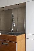 Chrome spray tap fitting over sink in modern kitchen