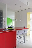 Sofa bottles on red worktop in modern kitchen