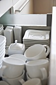 White tableware stored in open drawer