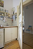 Corner of modern kitchen with view through open door to hallway