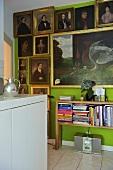 Ahnengalerie auf grüner Wand und halbhohes Bücherregal