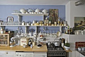 Kitchenware and tableware on shelves above kitchen worktop