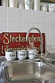 Küchenarmatur und Edelstahl-Spüle mit Vintage Metallgefässen