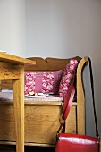 Pink cushions on wooden bench seat