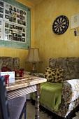 Antiker Holztisch vor altem Sessel und gelber Wand