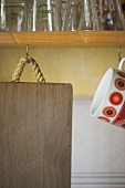 Wooden chopping board hanging from hook in shelf