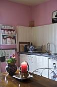 Brennende Kerze auf dem Tisch in ländlicher Küche mit weisser Holzverkleidung und rosa Wand