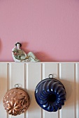 Two old-fashioned cake tins hanging on white wooden panelling