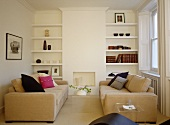 Pair of upholstered sofas facing each other in front of fireplace with built in shelving