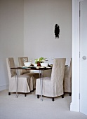 Linen covered chairs at table set for dinner in neutral colour dining room