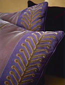 A detail of cushion with purple and gold design,
