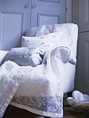 A detail of a bedroom, an upholstered armchair with cushions and draped organza embroidered fabric,