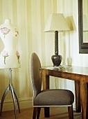 Schneiderpuppe neben grauem Polstersessel und Wandtisch mit Tischlampe
