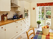Kitchen with white fitted units and French door to garden